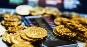 A stash of golden Bitcoins surrounding and on the face of a cellphone showing asset prices